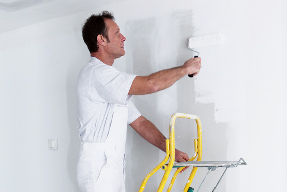 Painter rolling white paint on wall