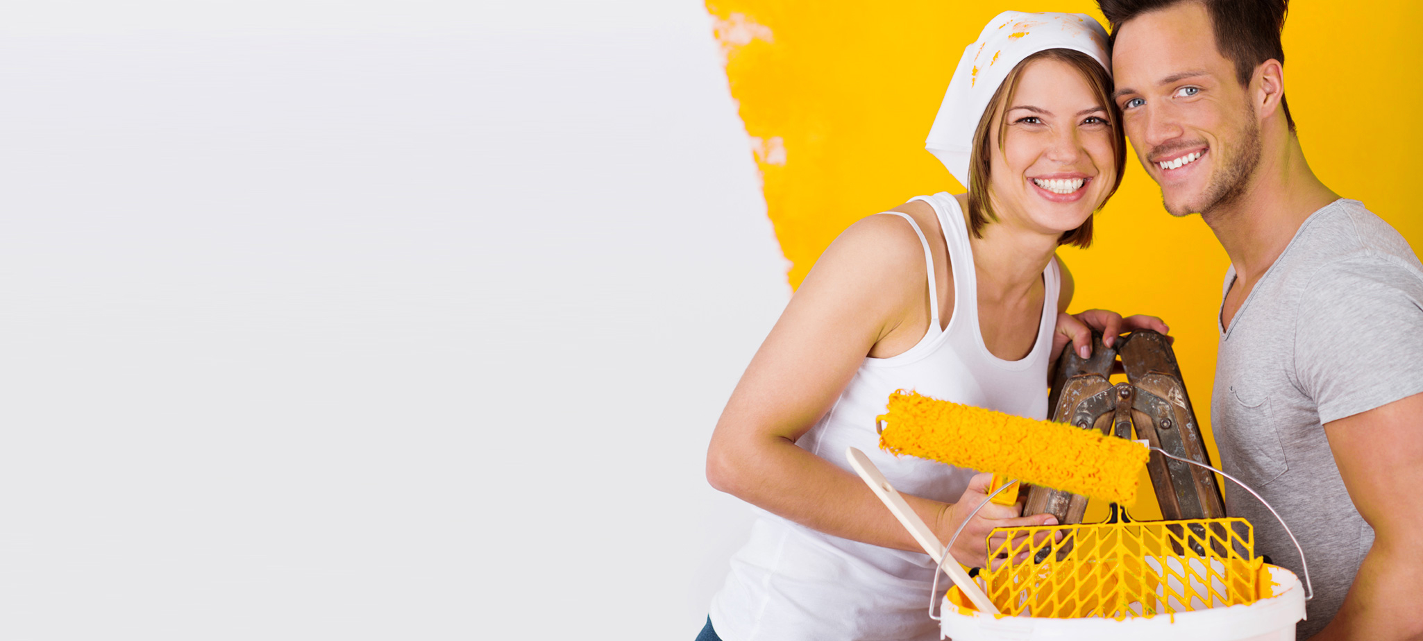 woman and man holding roller with yellow paint