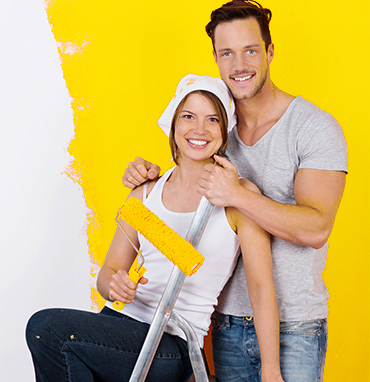 woman holding roller with yellow paint man standing
